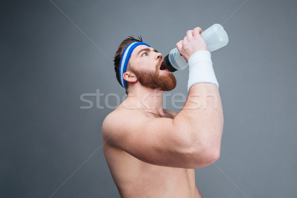 Shirtless bearded sportsman drinking water from plastic bottle Stock photo © deandrobot
