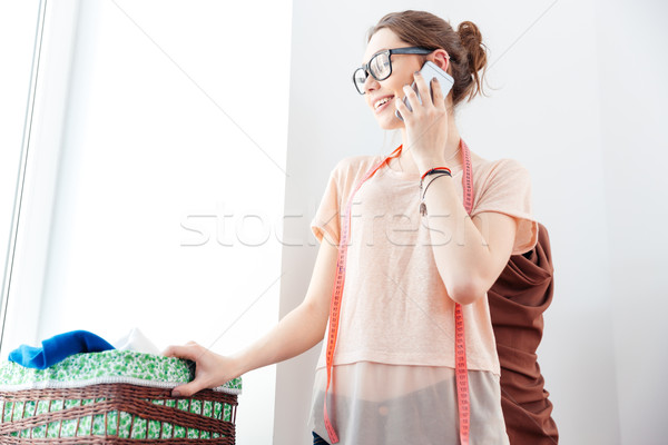 Happy woman seamstress looking at the window and using smartphone Stock photo © deandrobot