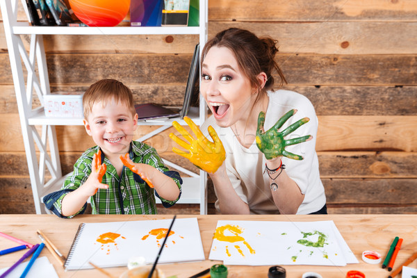 Smiling boy and mother showing hands painted in colorful paints  Stock photo © deandrobot