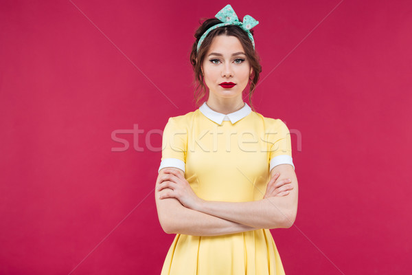 Beautiful serious woman in yellow dress standing with arms cross Stock photo © deandrobot