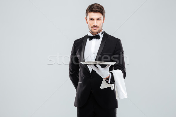 Handsome yong waiter in tuxedo and gloves holding empty tray Stock photo © deandrobot