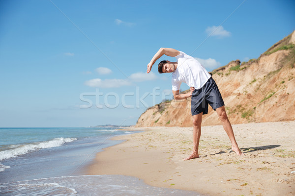 Man standing and working out on the beach Stock photo © deandrobot