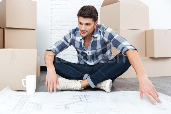 Stock photo: Handsome man looking at the house plan blueprint