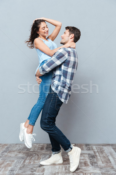 Man picking up and hugging his girlfriend over gray bakground Stock photo © deandrobot