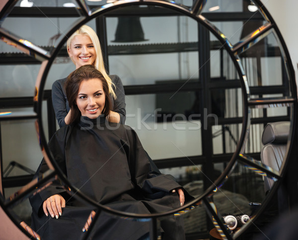 Reflection of hairdresser setting customer's hair Stock photo © deandrobot