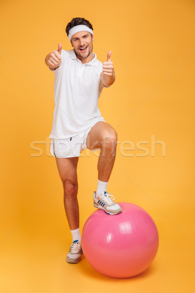 Sportsman with one foot on fitness ball showing thumbs up Stock photo © deandrobot