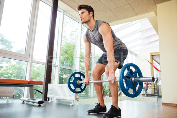 Sportsman standing and lifting barbell in gym Stock photo © deandrobot