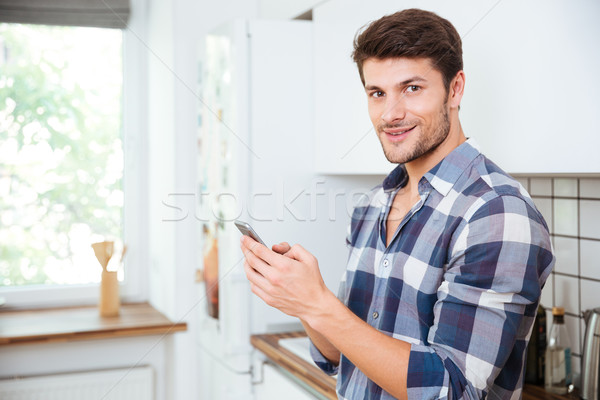 Stock photo: Happy young man using cell phone on the kitchen