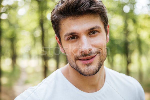 Happy handsome young man wearing white t-shirt in forest Stock photo © deandrobot