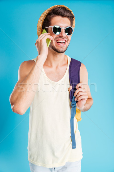 Smiling young man with backpack talking on cell phone Stock photo © deandrobot