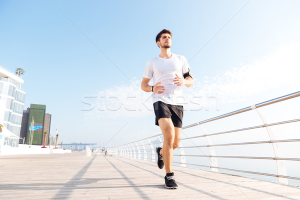 Concentrated young sportsman running on pier in the morning Stock photo © deandrobot