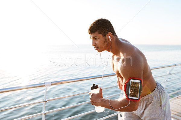 African american man athlete with blank screen smartphone in armband Stock photo © deandrobot