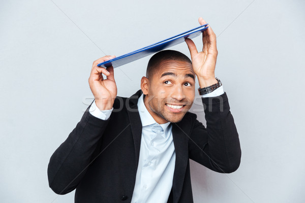 Smiling african american young man hiding under blue clipboard Stock photo © deandrobot