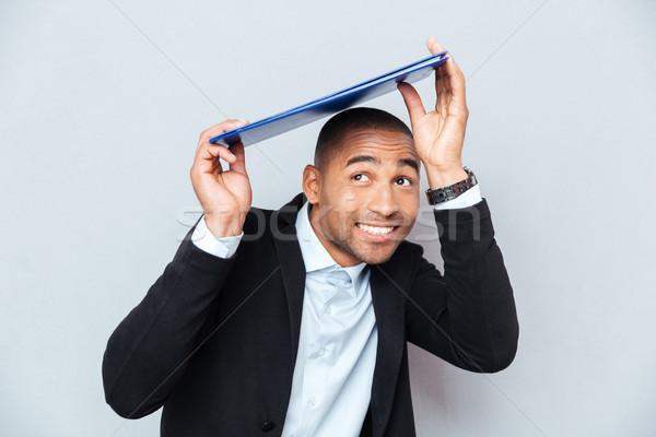 Mosolyog afroamerikai fiatalember rejtőzködik kék vágólap Stock fotó © deandrobot