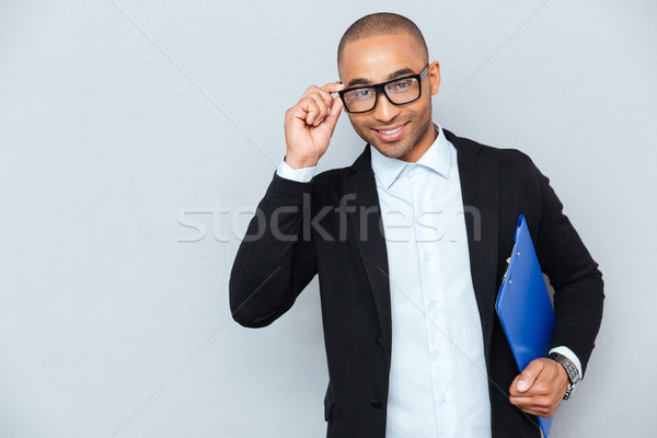 Cheerful african young businessman in glasses with blue folder Stock photo © deandrobot