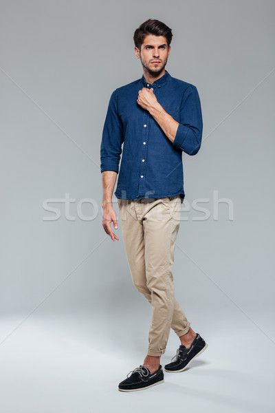Full length portrait of a casual young man fastening button Stock photo © deandrobot
