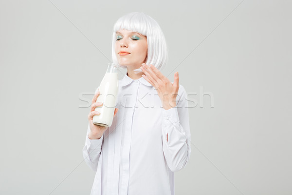 Attractive inspired young woman smelling milk in bottle Stock photo © deandrobot