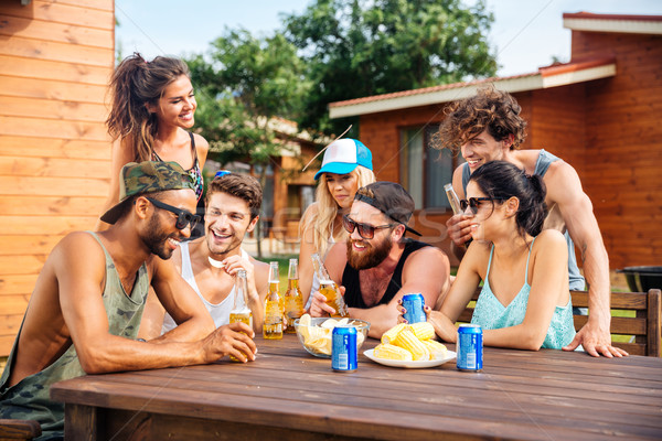 Cheerful young friends drinking beer outdoor summer party Stock photo © deandrobot