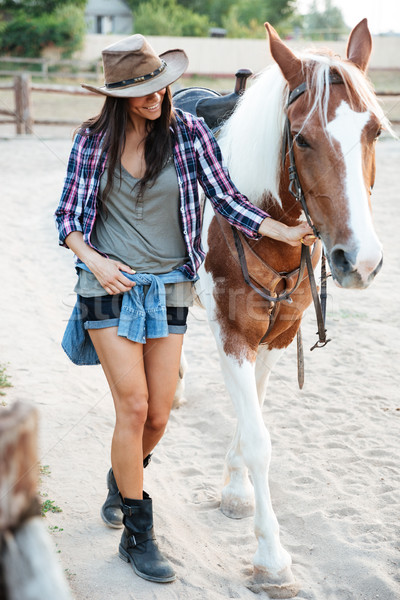 Cheerful cute young woman cowgirl walking with her horse Stock photo © deandrobot