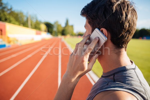 Side view of a male athlete talking on mobile phone Stock photo © deandrobot