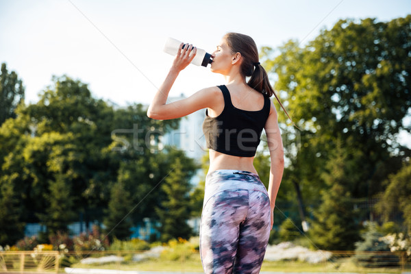 Female athlete drinking from water bottle after workout at stadium Stock photo © deandrobot