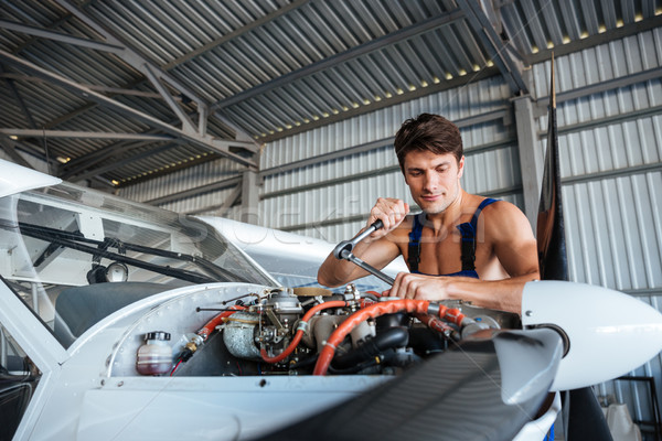 Serious young aircraft mechanic fixing small airplane Stock photo © deandrobot