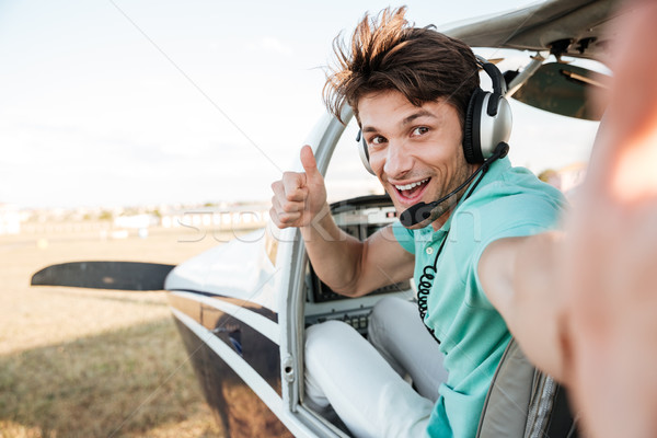 Cheerful pilot sitting in airplane cabin and showing thumbs up Stock photo © deandrobot