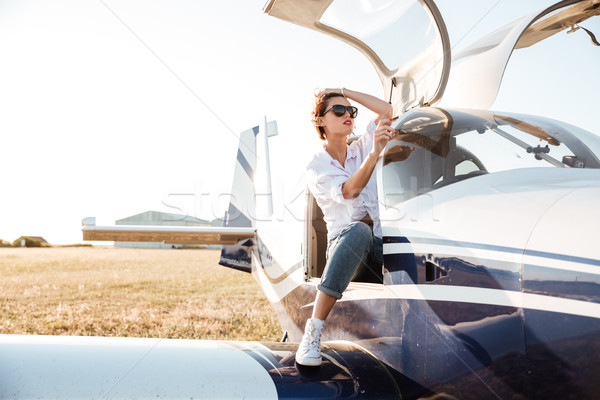 Woman in sunglasses sitting in small private plane Stock photo © deandrobot