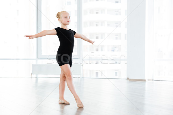 Little girl is busy performing ballet exercises Stock photo © deandrobot