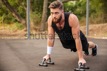 Handsome bearded sportsman doing push-ups outdoors Stock photo © deandrobot