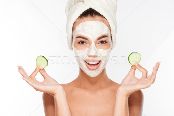 Woman with facial mask and cucumber slices in her hands Stock photo © deandrobot