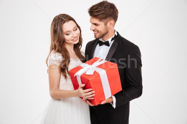 Ifjú pár ajándék izolált fehér mosoly férfi Stock fotó © deandrobot