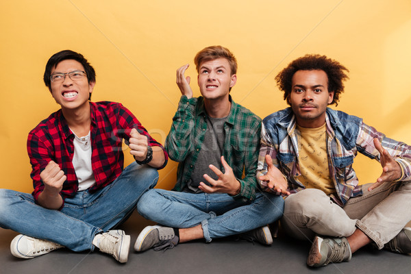 Three angry irritated young men friends sitting with legs crossed Stock photo © deandrobot
