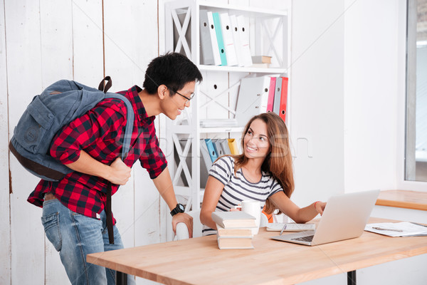 Cheerful female student pointing on display of laptop to groupmate Stock photo © deandrobot