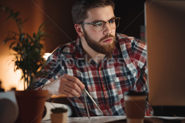 Bearded designer working late at night and looking on computer. Stock photo © deandrobot