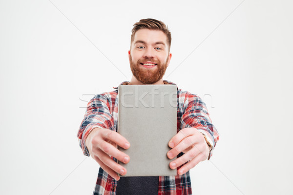 Smiling happy bearded man showing book cover to camera Stock photo © deandrobot