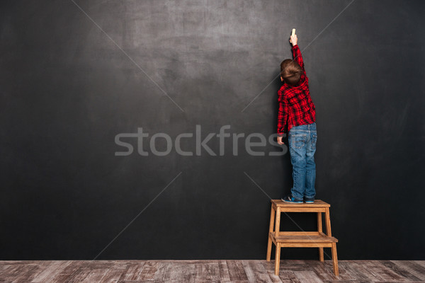 Child standing on stool near blackboard and drawing at board Stock photo © deandrobot