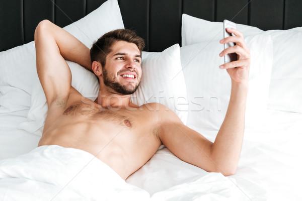 Stock fotó: Boldog · férfi · okostelefon · ágy · jóképű · fiatalember