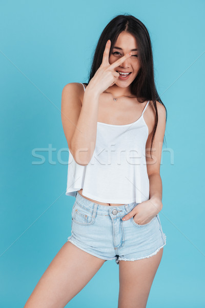 Portrait of a pretty excited woman showing victory sign Stock photo © deandrobot