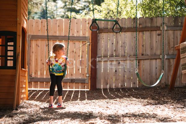 Kız salıncak görmek çit Stok fotoğraf © deandrobot