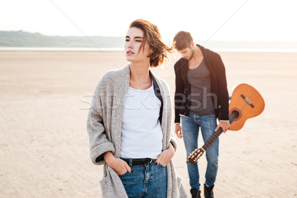 Beautiful young couple standing at the seashore with guitar Stock photo © deandrobot