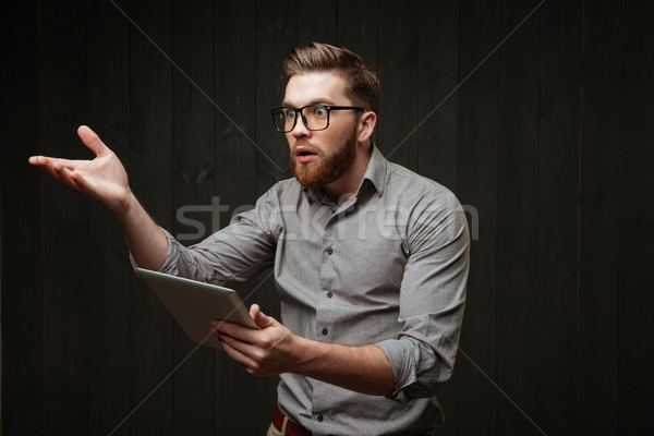 Surprised bearded man in eyeglasses holding tablet computer and gesturing Stock photo © deandrobot