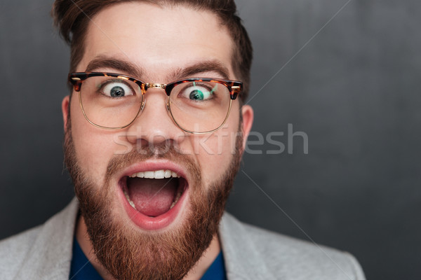 Surprised happy young businessman in glasses with opened mouth Stock photo © deandrobot