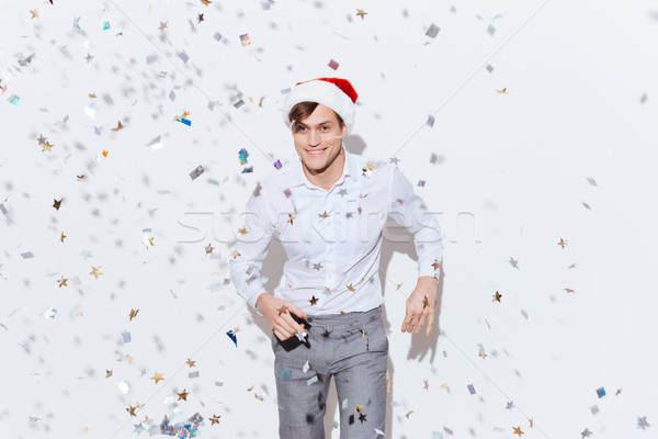 Happy young businessman in santa claus hat dancing and smiling Stock photo © deandrobot