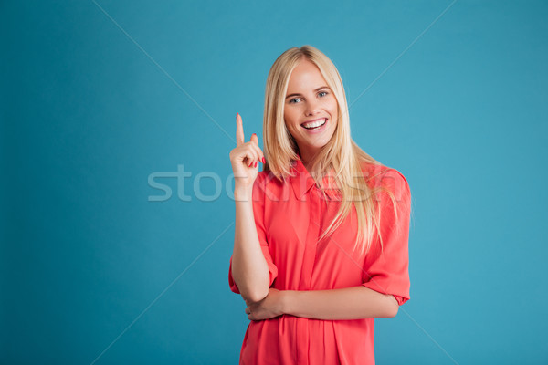 Stock photo: Smiling young happy woman poiting finger up at copyspace