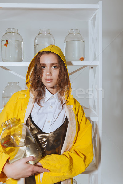 Pretty woman in yellow raincoat holding jar with gold fish Stock photo © deandrobot