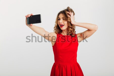 Kadın uzun kıvırcık saçlı ekran cep telefonu Stok fotoğraf © deandrobot