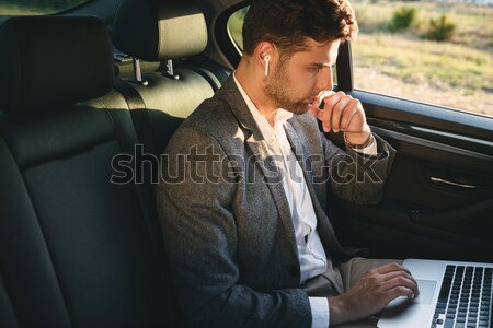 Thoughtful young businessman holding hand on forehead and looking away Stock photo © deandrobot