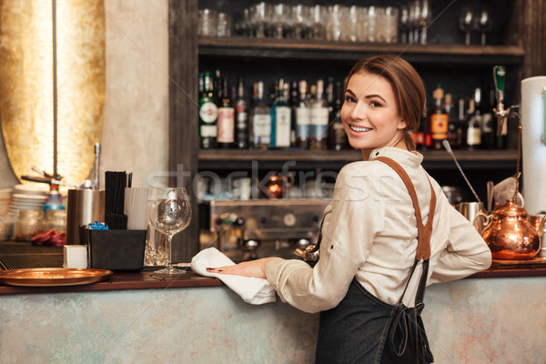 Young woman bartender standing in cafe. Stock photo © deandrobot