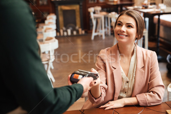 Attractive young pretty woman sitting in cafe pays the order Stock photo © deandrobot